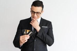 Young man in a suit looking thoughfully at a handful of credit cards.