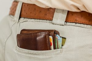 Man's back pocket with credit card filled wallet peaking out.