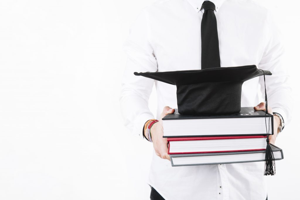 Man in white button up shirt with dark tie carrying textbooks with a graduation cap on the books.