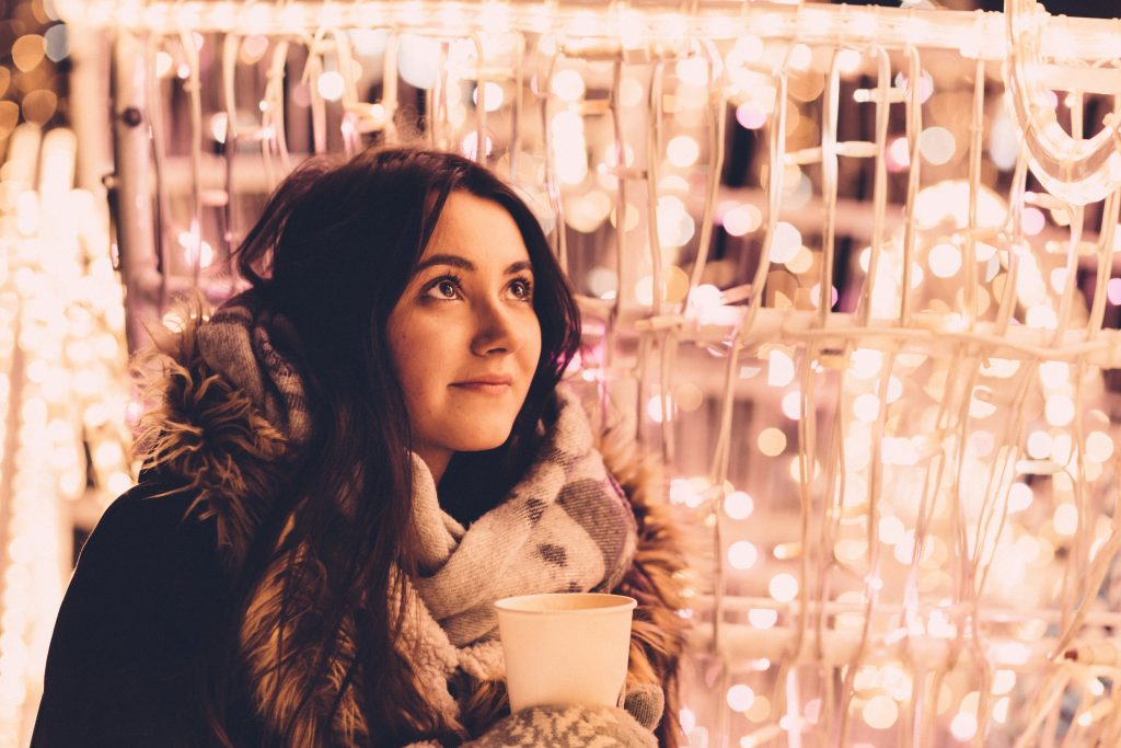 Young girl bundled up in coat, scarf and mittens with a hot drink in front of a wall of white lights.