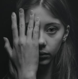 Young girl hiding the right hand side of her face with her hand