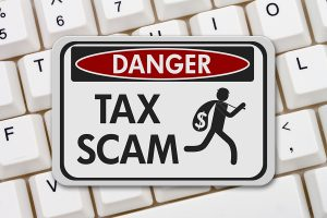 Tax scam danger sign, A black and white danger sign with text Tax Scam and theft icon on a keyboard